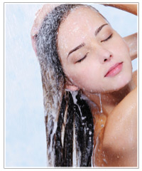 Woman washing shampoo from hair.