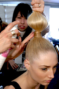 Applying hairspray to ponytail