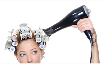 Model with a blow-dryer and hair in curlers.